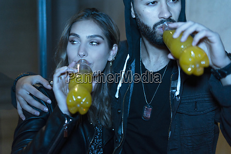 young couple with beverages outdoors in