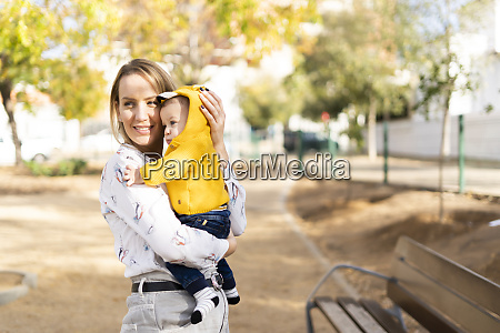 happy mother carrying baby boy in