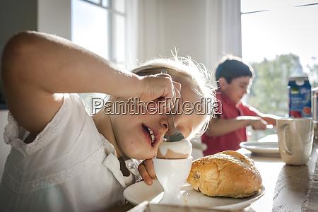 girl eating a boiled egg at