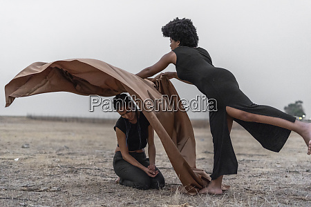 woman covering another woman with blanket