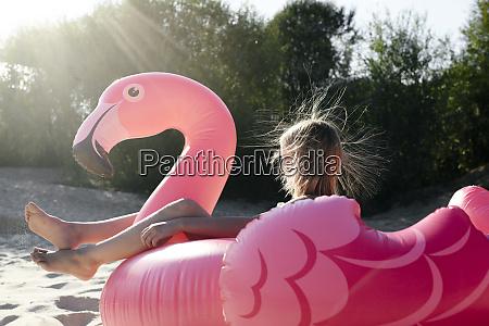 girl sitting on flamingo pool float