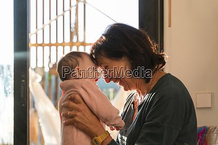 grandmother holding baby girl head on