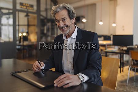 portrait of smiling senior businessman using