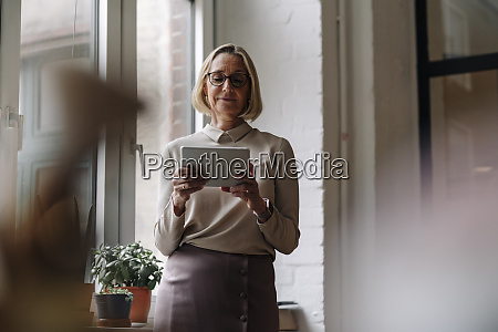 mature businesswoman using tablet at the