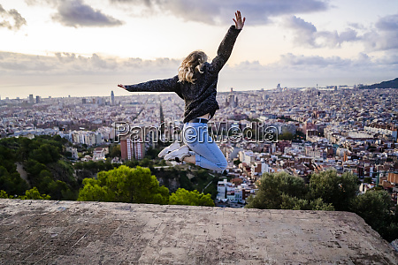 carefree young woman jumping above the
