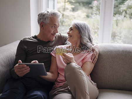 happy senior couple relaxing on couch