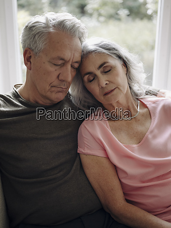 senior couple napping on couch at