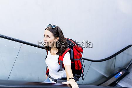 young female backpacker on escalator verona