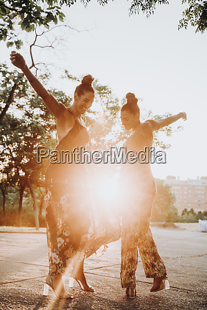 two cheerful twin sisters dancing outdoors