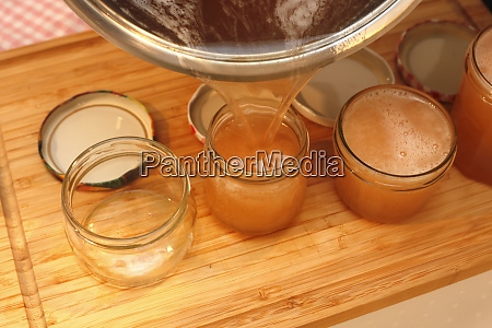 pouring quince jelly into jars