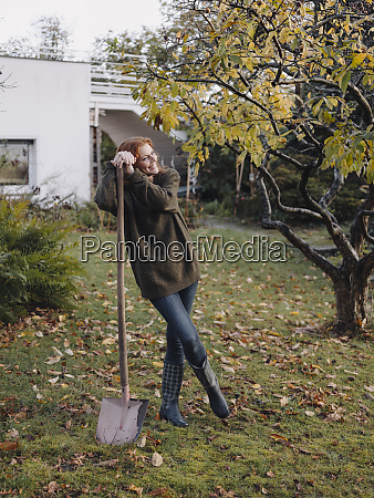 woman working in her garden holding