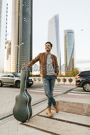 man with guitar in the city