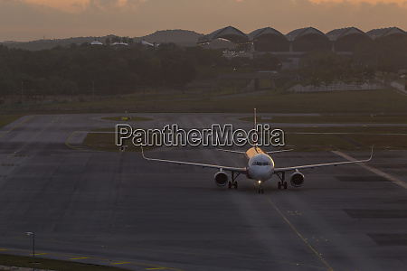 commercial airplane at airport at sunset