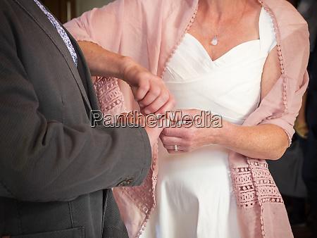 bride putting wedding ring on finger