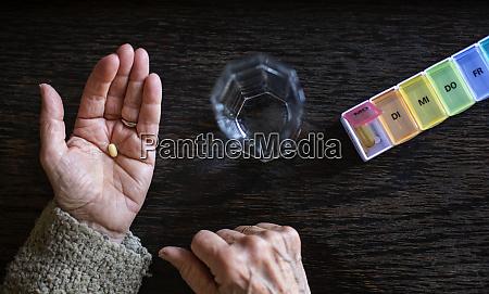 senior woman taking medicine water glass
