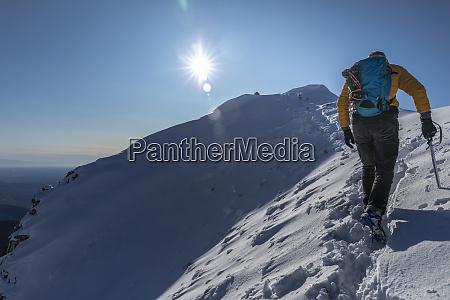 mountaineer hiking on snowy mountain lecco