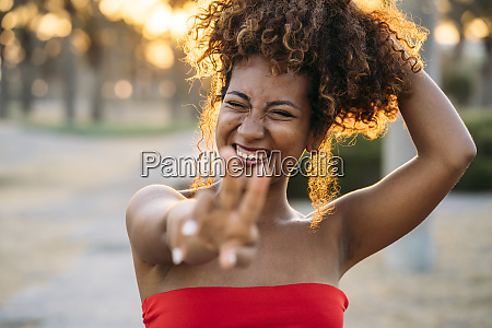 young happy woman expressing v gesture