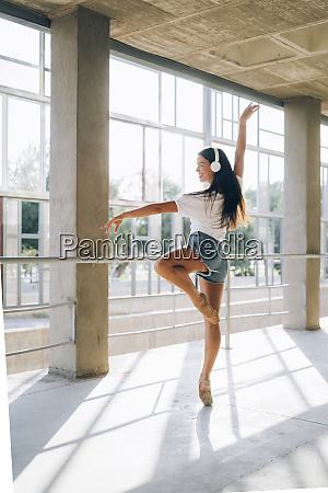 ballerina with headphone dancing in gym