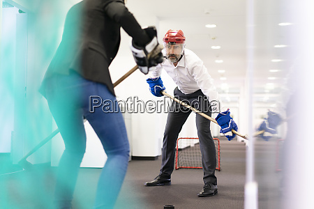 businesswoman and businessman playing ice hockey