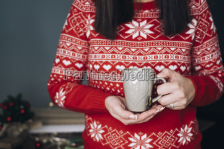 woman holding cup of tea in