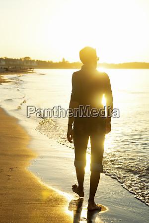man walking on the beach at
