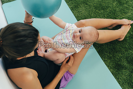 young mother and baby exercising on