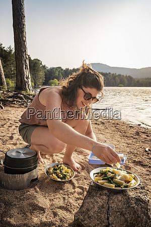 woman garnishing pasta dish with parmesan