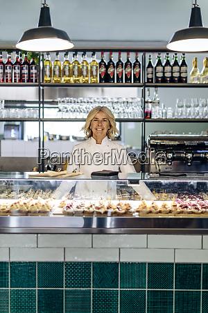 proud bistro woner standing behind pastry