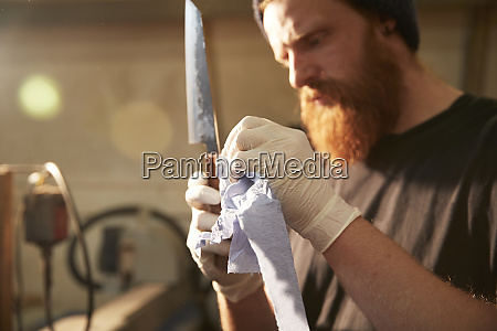 man making knives in a workshop