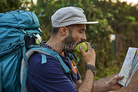backpacker biting an apple and checking