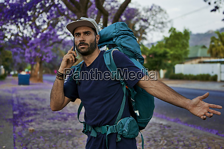 backpacker standing on a street using