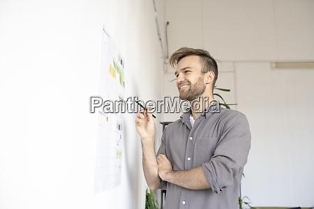 smiling man working on paper at