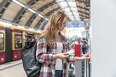 woman at train station buying train