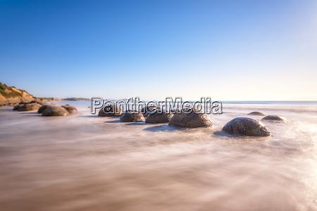 moeraki boulders in sea against sky