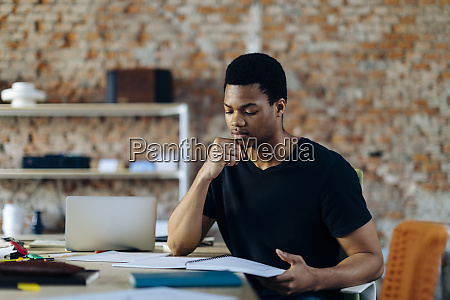 young man sitting at table looking