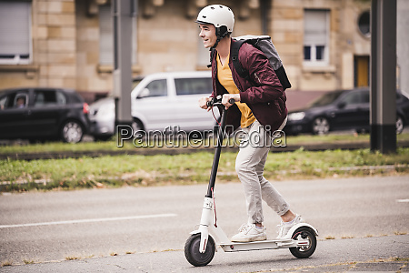 smiling young man riding scooter in