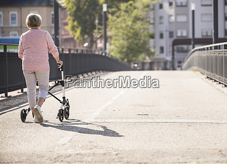 senior woman with wheeled walker on