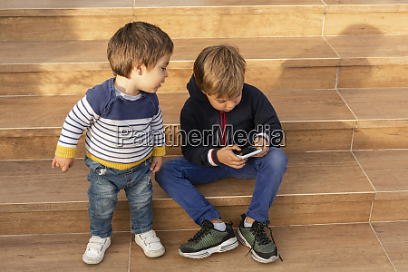 two little boys looking at cell