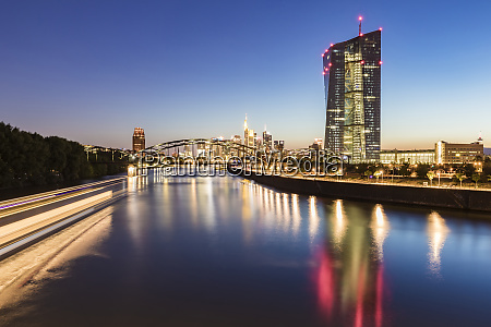 river in illuminated city against blue