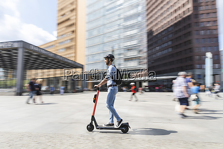 businessman riding e scooter on the