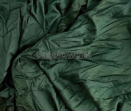green satin textile fabric piece of