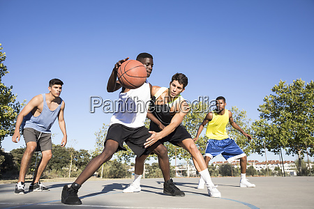 young men playing basketball and dribbling
