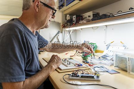 senior man working on electronic circuits