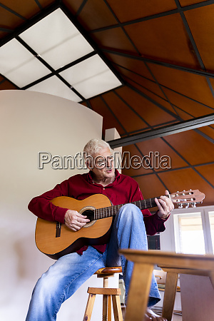 senior man playing guitar at home