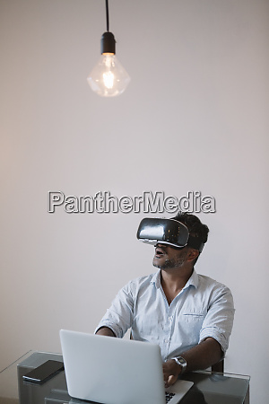 businessman sitting at table testing vr