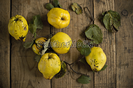 fresh yellowquinces lying on wooden surface