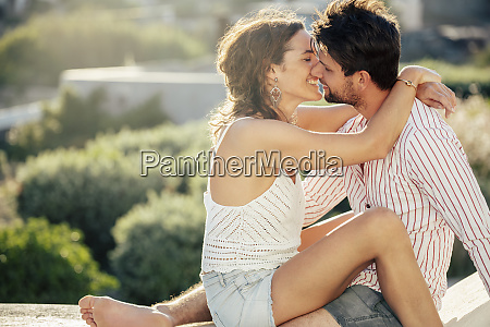 romantic couple sitting on wall embracing
