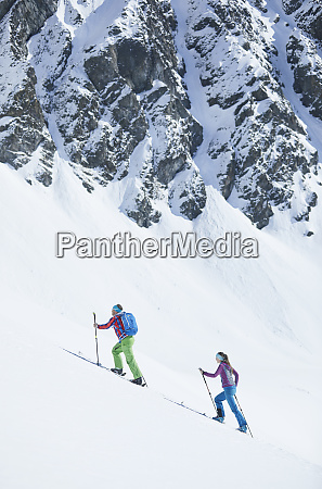 couple ski touring in the mountains
