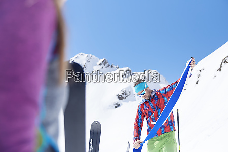 ski tourer removing pelt from ski