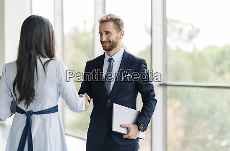 businessman and businesswoman shaking hands at